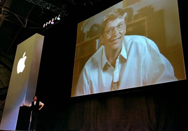Ngày 04/7/1997, Jobs đã thành công trong việc thuyết phục Hội đồng quản trị của công ty thay thế Amelio – CEO đương nhiệm - bằng chính bản thân mình. Tháng 8/1997 tại Macworld Expo, bất chấp sự phản đối của người dùng, Apple nhận khoản đầu tư 150 triệu USD từ đối thủ lâu năm Microsoft. Ảnh: Reuters.