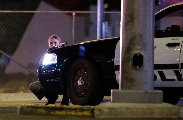 Một cảnh sát của Las Vegas núp sau chiếc xe ô tô làm nhiệm vụ. Ảnh: AP