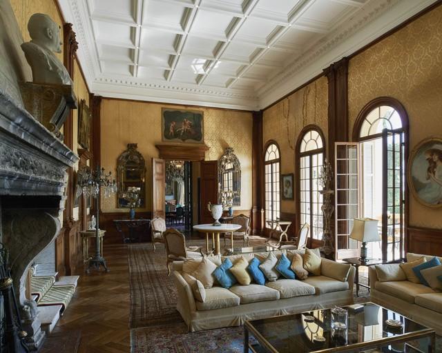 Một phòng khách ở tầng trệt ghi đậm dấu ấn của những chủ nhân cũ, đặc biệt là Vua Leopold II, với hoàng huy gắn trên một trong những bức tường phủ bằng lụa