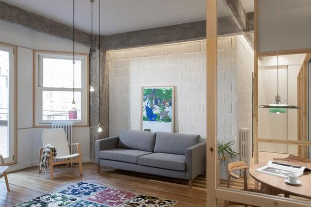 Sofa màu ghi được kê sát tường gạch trần màu trắng, thêm một vài điểm nhấn từ ánh sáng thả trần, dịu dàng và ấm cúng.