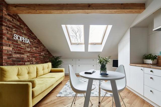 Bức tường gạch trần vuông góc với cửa sổ, giữ nguyên gam màu của gạch để tăng diện tích về mặt thị giác. Sofa vàng được đặt sát tường, với gam màu tươi tắn, dịu dàng đủ để không gian nhỏ trở nên xinh yêu và đặc biệt trong mắt mọi người khi ngắm nhìn.