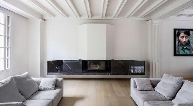 Mặc dù bên ngoài được ngụy trang kiểu nhà gỗ nhưng phía bên trong ngôi nhà lại được cải tạo vô cùng hiện đại. Sắc trắng tinh khôi khiến phòng khách như rộng lớn hơn. Với cách phối màu ghế, gối xám trắng giản đơn, điểm thêm một số kệ tường màu đen khiến phòng khách này càng thêm nổi bật.