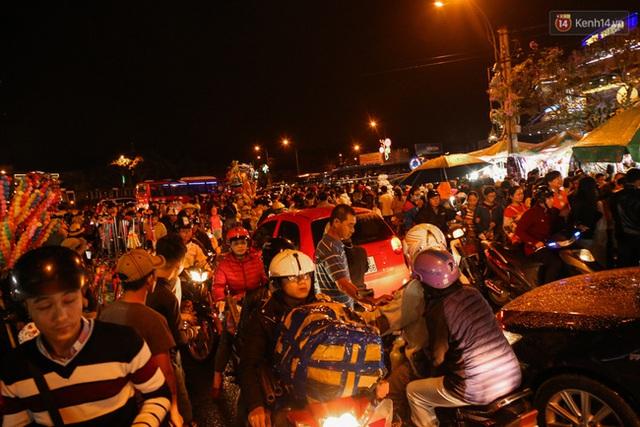 Xe máy và ô tô ùn ùn ra vào phố đi bộ mặc nhiều người đang tản bộ.