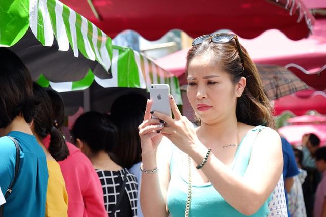 Một nữ du khách thích thú chụp ảnh buôn bán tấp nập tại phố hàng rong.