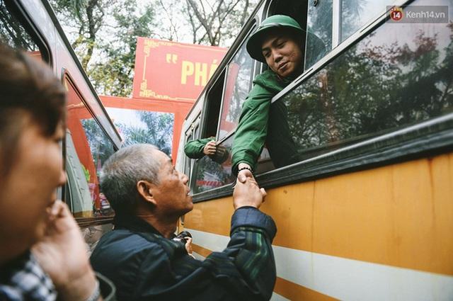 Người bố nắm chặt tay con trai trước khi xe khởi hành với lời chúc may mắn, hoàn thành xuất sắc nhiệm vụ trở về.