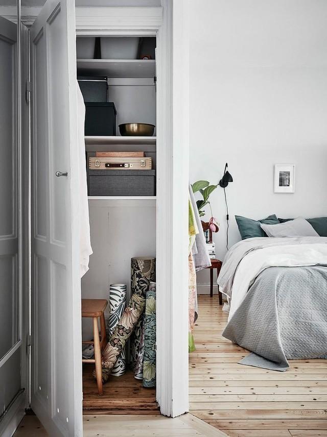 Một hệ tủ dài cao sát tường ngăn bên ngoài chủ nhà dùng để trữ vật dụng và ngăn bên trong là tủ đựng quần áo vào đồ dùng cá ngân thuận tiện ngay cạnh giường ngủ.