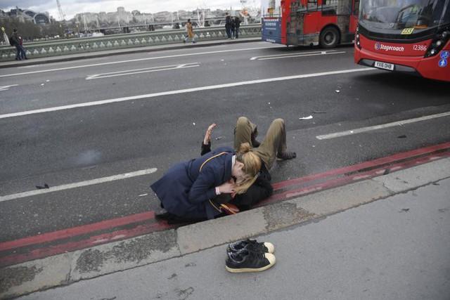 Người phụ nữ giúp đỡ một người bị thương trong vụ tai nạn trên cầu Westminster ở London, ngày 22 tháng 3.