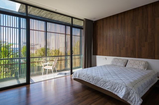 Phòng ngủ chính trong ngôi nhà với hệ cửa được thiết kế kiểu lam gỗ chắn nắng và đảm bảo sự riêng tư.