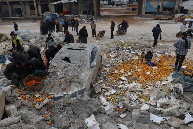 Người dân thu nhặt những quả cam giữa đống đổ nát sau một cuộc không kích vào khu chợ do phiến quân tổ chức tại thành phố Maarrat Misrin ở tỉnh Idlib, Syria vào ngày 14 tháng 1.
