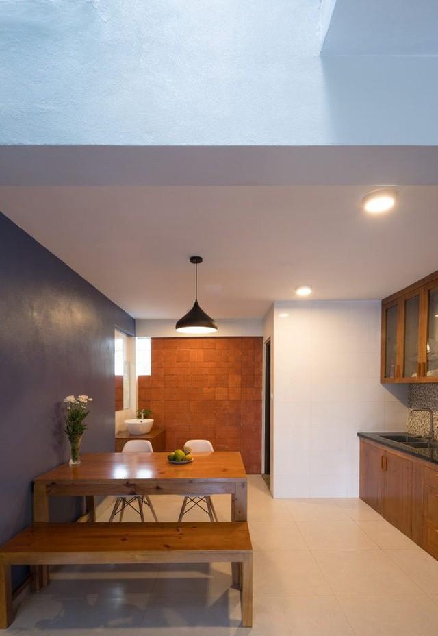 Khu bếp và bàn ăn bố trí đối diện với nhau. Nhờ khoảng thông tầng và những ô gạch kính đằng sau mà không gian này vẫn thoáng và đủ sáng.