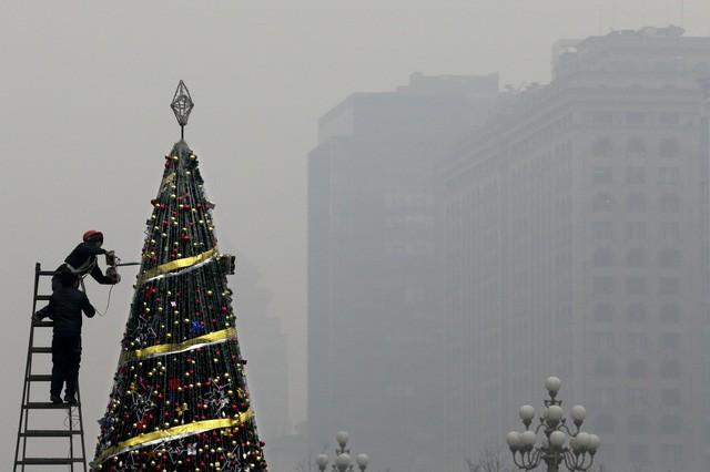 Một người thợ đang tu sửa cây thông Noel khổng lồ tại thành phố Bắc Kinh giữa bầu không khí không được trong lành cho lắm.