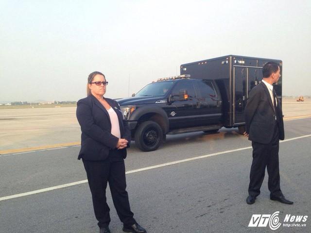 Mật vụ Mỹ đứng bên xe chuyên dụng của Đơn vị Xử lý Vật liệu Độc hại trong đoàn xe hộ tống Tổng thống Mỹ tại sân bay Nội Bài, chiều 11/11. (Ảnh: Hữu Dánh)