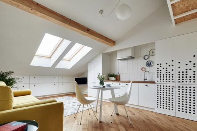 Khu vực nấu nướng được bố trí đối diện với nơi tiếp khách. Không gian được sắp xếp hệ thống tủ đựng đồ tiện lợi và liền mạch bằng màu sắc trắng tinh.