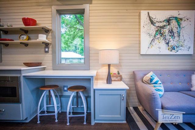 Góc tiếp khách được đặt ngay lối vào nhà với thảm trải sàn sọc đen trắng tăng nét độc đáo và bắt mắt cho góc nhỏ. Thêm vào đó là một chiếc sofa dài kê sát tường nhằm tiết kiệm diện tích và giúp mọi người sống tiện nghi hơn.