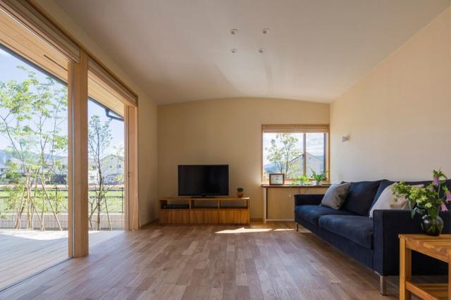 Phòng khách rộng rãi thoáng mát được thiết kế gọn gàng với ghế sofa kê dọc bức tường. Từ phòng khách có thể nhìn ra khoảng sân rộng thoáng trồng nhiều cây xanh phía ngoài.