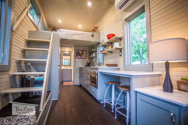 Không gian bếp núc được đặt bên trong phòng khách. Bếp được trang trí đơn giản với hệ thống tủ nhiều ngăn thỏa mãn nhu cầu trữ đồ của chủ nhà.