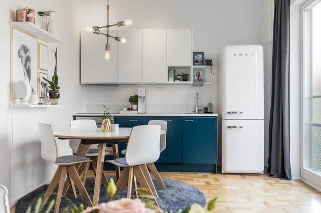 Cũng trên tông màu trắng chủ đạo nhưng góc bếp nhỏ xinh lại được nhấn nhá bằng khoảng xanh mát mắt của hệ kệ tủ và chiếc thảm lớn tối màu dưới bàn ăn. Trên bức tường nơi góc bếp còn được tô điểm bằng những bức trang nghệ thuật xinh xắn và cây xanh.