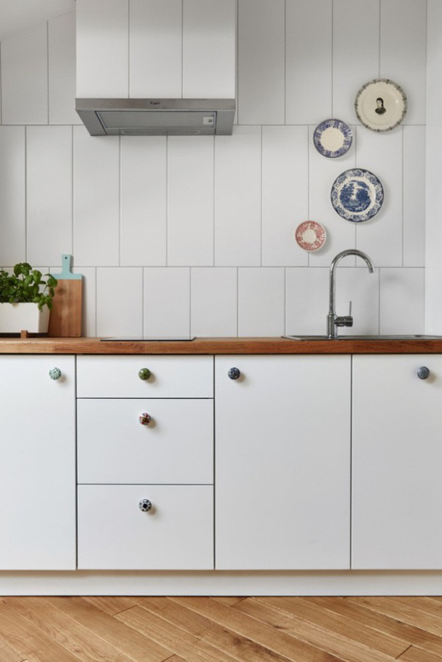 Bếp nếu dù nhỏ nhưng vẫn không quên mang theo nét độc đáo và tính tế nhờ những núm cửa tủ và điểm nhấn trên tường với họa tiết từ đĩa gốm sứ.