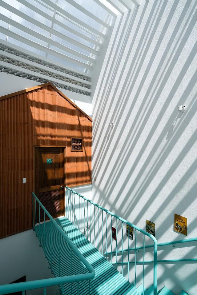 Hệ cầu thang bằng thép màu sắc và mặt tiền độc đáo tạo sự riêng tư cho các phòng.