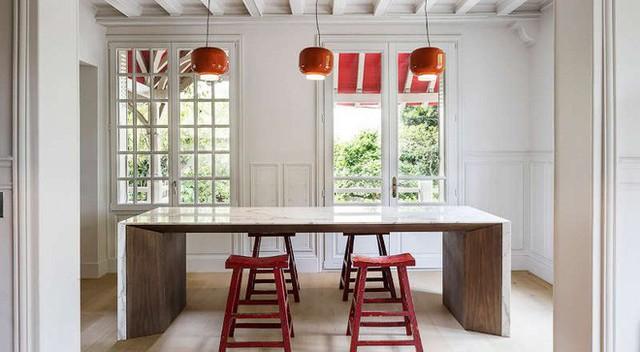 Nhà bếp là nơi không cần thiết sử dụng tường sơn màu quá trắng. Nhưng để trông tổng thể vẫn đồng đều một cách tương đối, chủ nhà đã khéo léo sơn tường, trần nhà màu trắng ngà, vô cùng hài hòa và khiến những chiếc ghế đỏ nổi bần bật.
