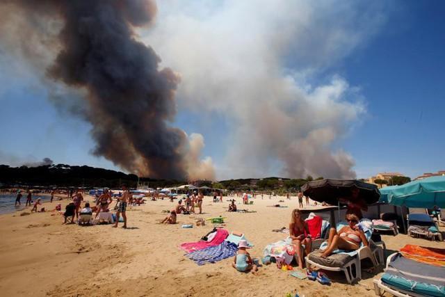 Khói tràn ngập bầu trời trên một ngọn đồi đang cháy trong khi khách du lịch vẫn nghỉ ngơi trên bãi biển ở Bormes-les-Mimosas, thuộc tỉnh Var, Pháp, ngày 26 tháng 7.