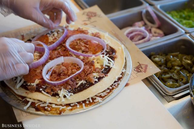 Một đơn đặt hàng pizza đang được chuyển đến 1 hộp nhỏ giao hàng có 1 nắp tháo rời. Nó cải thiện bí kíp của ăn ngoài hộp vì không có vạt bìa cứng treo trên lòng khách mua.