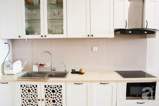 Bếp nấu được bố trí đối diện với bàn ăn, vẫn trừ lại khoảng diện tích khá rộng làm lối đi. Khu vực bếp được bố trí hệ thống tủ gắn tường màu trắng ngà.