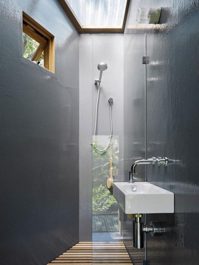 Một góc nhỏ dành cho chức năng thư giãn, tắm táp hàng ngày. Khu vực tuy chỉ vài mét vuông nhưng cũng đủ để kiến trúc sư thiết kế phòng tắm đứng, sàn gỗ thoát nước ra bên ngoài, cửa kính để kết nối bên trong và bên ngoài một cách tiện lợi.