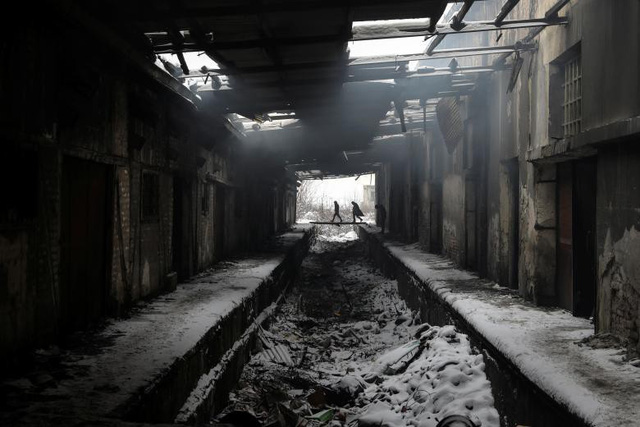 Những người di cư đang đi giữa thời tiết lạnh giá tại một nhà kho hải quan bỏ hoang ở Belgrade, Serbia, ngày 11 tháng 1.