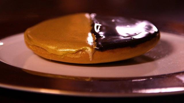 Đây là sự phối hợp giữa bánh quy cổ điển với socola đen và trắng, bụi vàng 24K trộn với ngọc trai trắng phủ lên một nửa chiếc bánh.