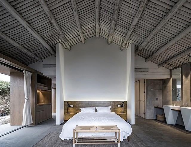 Phòng ngủ chính rộng lớn tạo cảm giác hiện đại pha lẫn mộc mạc nhờ nội thất bằng gỗ và bê tông.