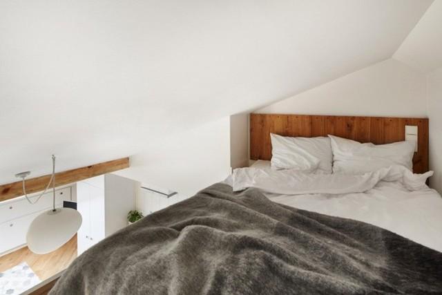 Giường ngủ được thiết kế đơn giản với nệm, khoảng diện tích đầu giường ốp gỗ tạo điểm nhấn bắt mắt cho không gian nghỉ ngơi.