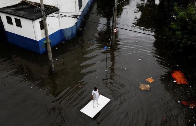 Một công nhân sử dụng chiếc bàn để di chuyển dọc theo con đường ngập lụt sau mưa lớn tại Sao Paulo, Brazil ngày 7 tháng 4.