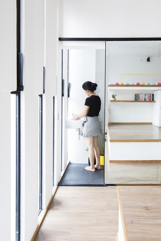 Phòng vệ sinh nhỏ với cánh cửa trượt bằng gương giúp không gian thêm rộng rãi.