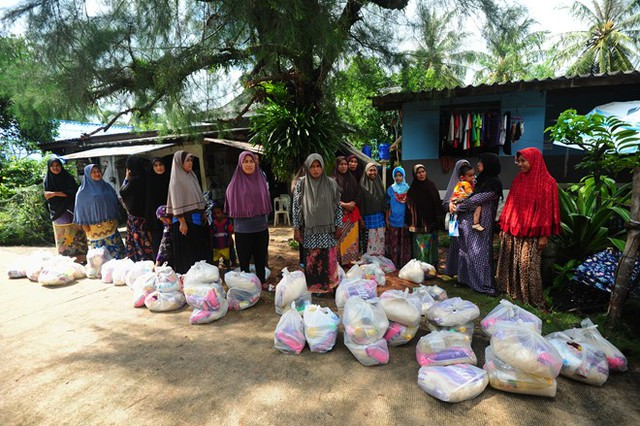Người dân tỉnh Narathiwat nhận hàng hóa cứu trợ. Ảnh: AFP.