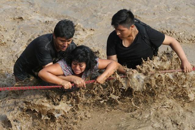 Người dân đang vượt qua một con đường ngập lụt sau khi vụ lở đất lớn và lũ lụt ở quận Huachipa, Lima, Peru xảy ra vào ngày 17 tháng 3.