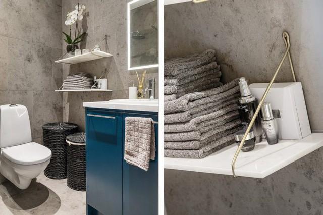 Nhà tắm không rộng nhưng được thiết kế khéo kéo với hệ thống tủ kệ và những giá treo thuận tiện để đựng đồ. Việc lựa chọn tông màu xanh và nâu mang lại cảm giác sạch sẽ cho khu vực nhà tắm.