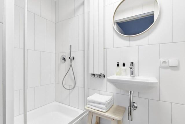 Phòng tắm màu trắng tinh khôi với đầy đủ các khu vực chức năng như bồn tắm, chậu rửa mặt, giá để khăn tắm… Ánh sáng màu trắng như mở rộng thêm diện tích một cách tối đa cho không gian thư giãn hàng ngày của gia đình.