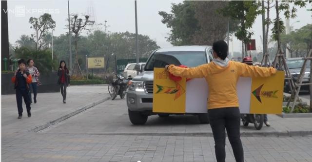 Bà mẹ người Hàn Quốc cầm biển báo ngăn dòng xe máy chạy lên vỉa hè tại Mễ Trì.