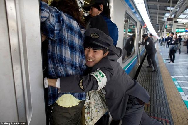 Nghề nhồi khách lên tàu điện ngầm cho kịp giờ khiến người ta chỉ biết thốt lên: Đúng là chỉ có ở Nhật Bản! - Ảnh 1.