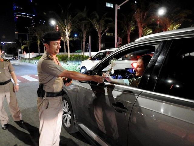 Ả Rập: Các sĩ quan cảnh sát đứng tặng hoa mừng ngày phụ nữ được phép lái xe ra đường - Ảnh 2.