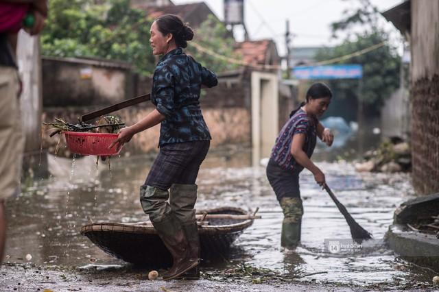 Chùm ảnh: 1 tuần sau lũ lớn, người dân Hà Nội vẫn phải chèo thuyền di chuyển giữa biển rác thải nổi lềnh bềnh - Ảnh 20.