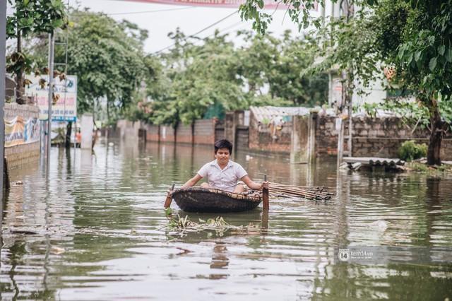 Chùm ảnh: 1 tuần sau lũ lớn, người dân Hà Nội vẫn phải chèo thuyền di chuyển giữa biển rác thải nổi lềnh bềnh - Ảnh 3.