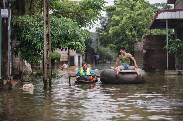 Chùm ảnh: 1 tuần sau lũ lớn, người dân Hà Nội vẫn phải chèo thuyền di chuyển giữa biển rác thải nổi lềnh bềnh - Ảnh 4.