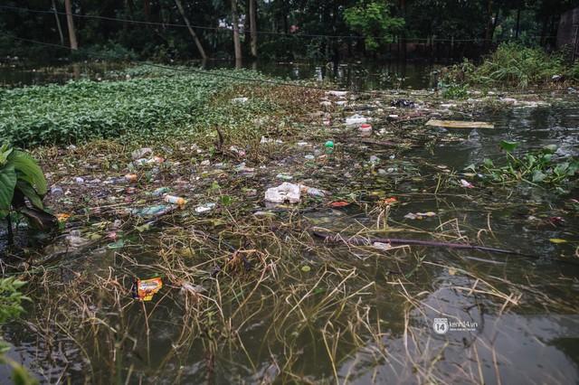 Chùm ảnh: 1 tuần sau lũ lớn, người dân Hà Nội vẫn phải chèo thuyền di chuyển giữa biển rác thải nổi lềnh bềnh - Ảnh 9.