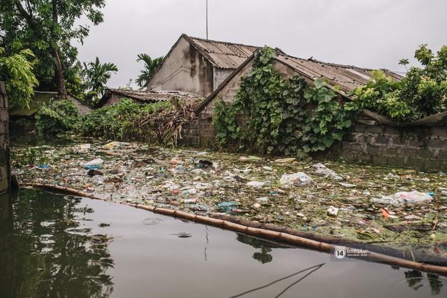 Chùm ảnh: 1 tuần sau lũ lớn, người dân Hà Nội vẫn phải chèo thuyền di chuyển giữa biển rác thải nổi lềnh bềnh - Ảnh 10.