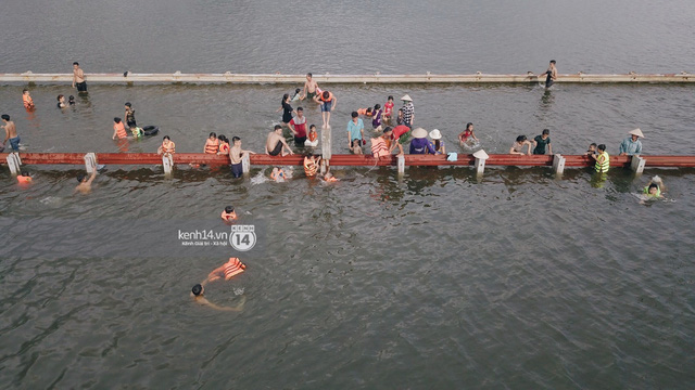 Nước vừa rút lại lên, người già trẻ nhỏ tiếp tục ùa ra đường tỉnh lộ vô tư bơi lội khi phương tiện bị cấm lưu thông - Ảnh 10.