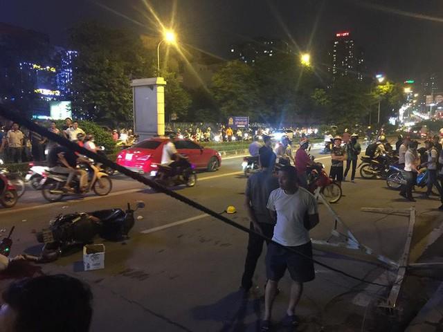 Thanh sắt giàn giáo rơi xuống đường giờ cao điểm đè trúng 3 xe máy, 1 phụ nữ tử vong - Ảnh 1.