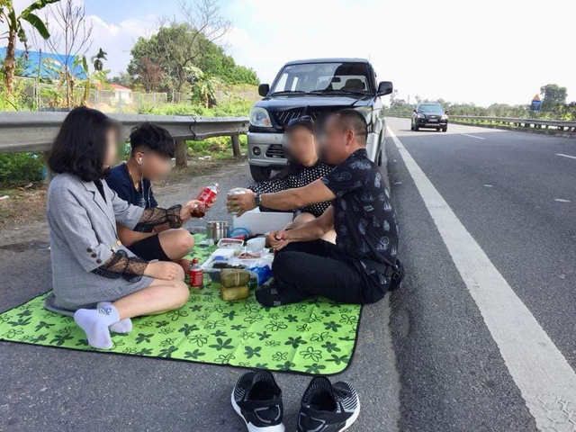 Hình ảnh gây phẫn nộ: Cả gia đình trải bạt, ăn uống trên cao tốc Nội Bài - Lào Cai bất chấp dòng phương tiện chạy rầm rập - Ảnh 1.