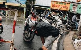 Người Sài Gòn chui hàng rào thép gai để giao hàng vì chốt chặn một số nơi chưa được tháo gỡ
